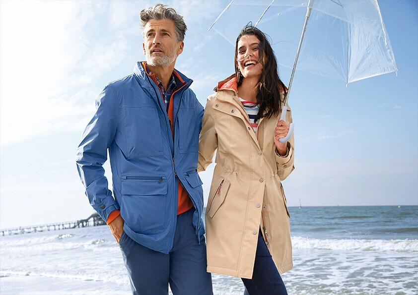 Man und Frau mit Regenschirm am Strand