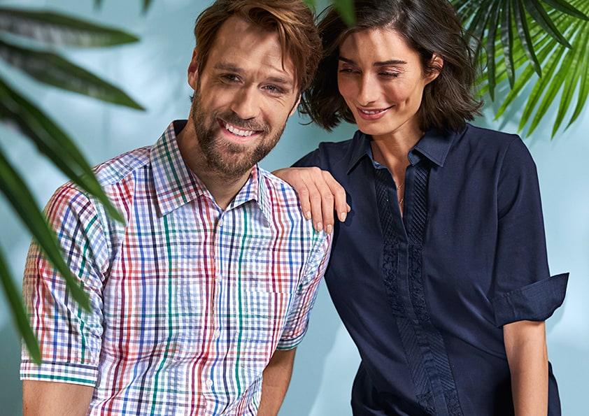 Mann im Karohemd und Frau in blauer Bluse stehen zwischen Palmenblättern
